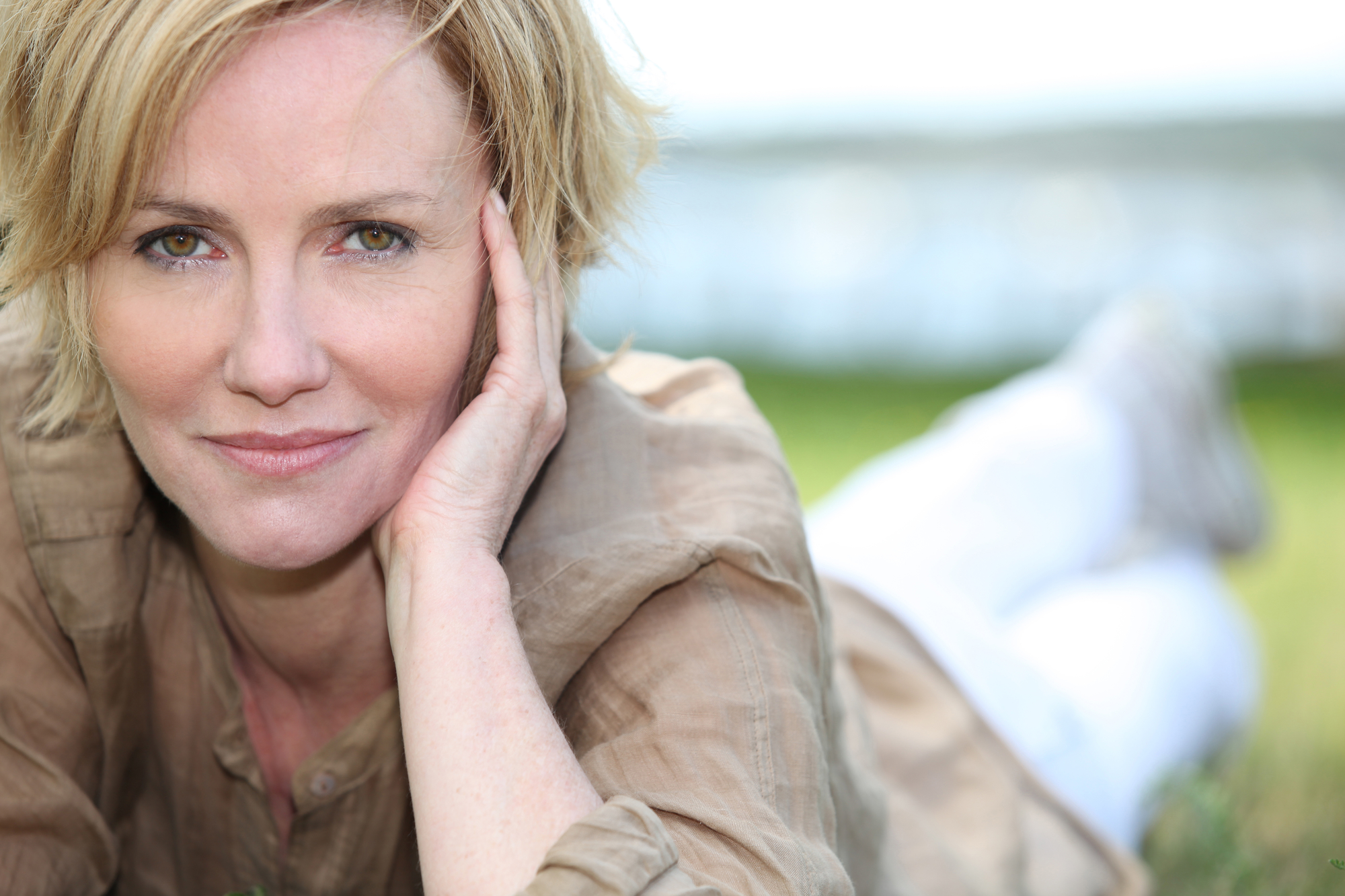 Portrait of magnificent mature blonde lying on grass - Frisco Women's Health
